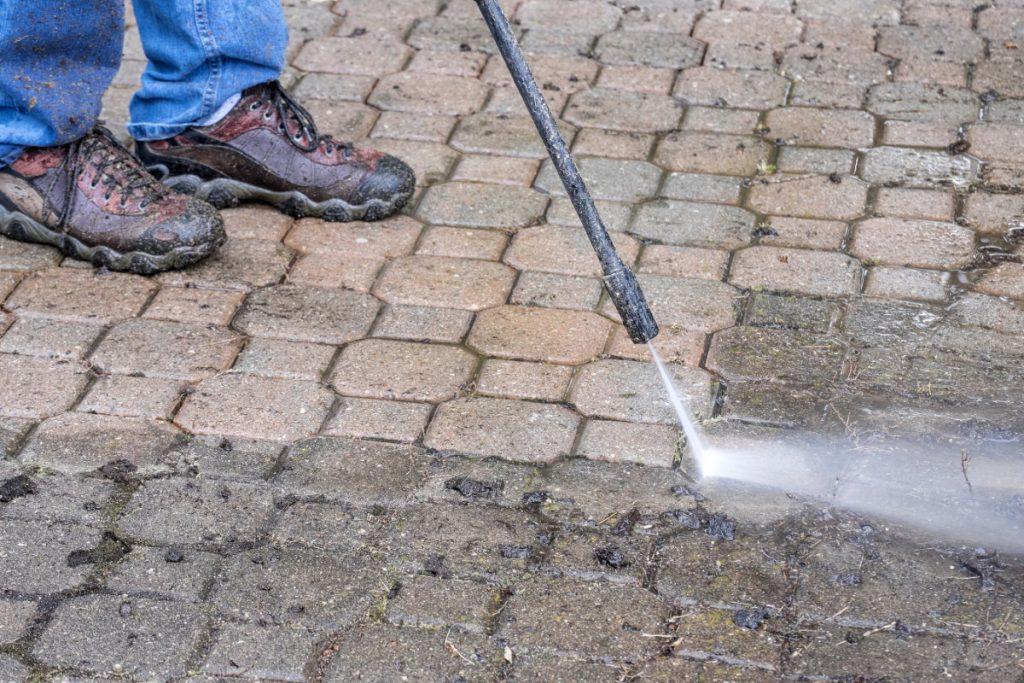 tegels van je tuin schoonpuiten met een hogedrukspuit